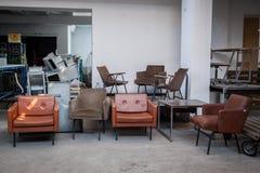 从70 ` s的葡萄酒皮革扶手椅子待售在一个古董商的仓库里在跳蚤市场上 免版税库存图片