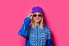 90s粗呢夹克和帽子的女孩有太阳镜的 免版税库存图片