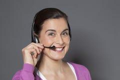 30s美丽的女实业家兴奋使用耳机作为电话 免版税图库摄影