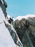 S'élever de glace : alpiniste sur un itinéraire mélangé de duri de neige et de roche photo stock