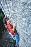 S'élever de hard rock grimpeur de roche émotif d'homme s'élevant sur la falaise photos libres de droits