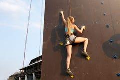 S'élever de pratique de jeune femme forte caucasienne sur le mur artificiel de roche dehors Vitesse blonde sportive mince de form photographie stock libre de droits