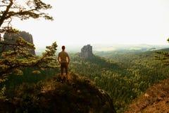 S'élever de touristes grand sur la falaise pointue et belle vue de négligence au-dessus de soufflet de vallée de forêt photos stock