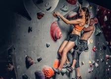 S'élever masculin et femelle sur un mur s'élevant photographie stock libre de droits
