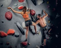 S'élever masculin et femelle sur un mur s'élevant d'intérieur photographie stock libre de droits
