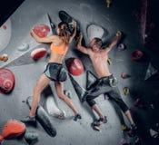 S'élever masculin et femelle sur un mur s'élevant d'intérieur image libre de droits