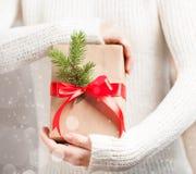 ` S женщины вручает держать подарочную коробку с яркой красной смычка, рождества и Нового Года, запачканным снегом, концом концеп Стоковое Изображение RF