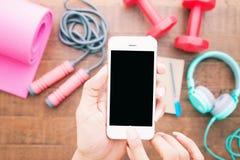 ` S женщины вручает держать smartphone пустого экрана и фитнес спорта Стоковые Фото