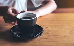 ` S женщины вручает держа и выпивая кофе на деревянной винтажной таблице Стоковая Фотография