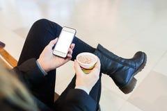 ` S женщины вручает держать smartphone и чашку капучино Стоковое Фото