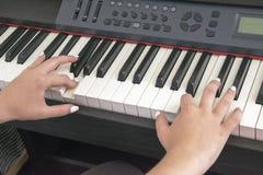 ` S женщины вручает играть на электрическом рояле стоковое изображение rf