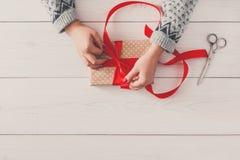 ` S женщины вручает оборачивать праздник рождества присутствующий с красной лентой Стоковые Фото