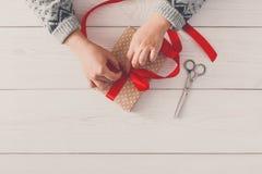 ` S женщины вручает оборачивать праздник рождества присутствующий с красной лентой Стоковая Фотография