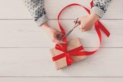 ` S женщины вручает оборачивать праздник рождества присутствующий с красной лентой Стоковое Изображение RF