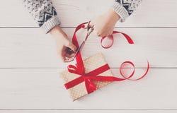 ` S женщины вручает оборачивать праздник рождества присутствующий с красной лентой Стоковое Изображение