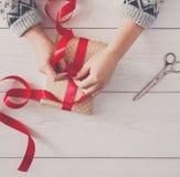` S женщины вручает оборачивать праздник рождества присутствующий с красной лентой Стоковые Изображения