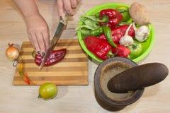 ` S женщины вручает перец вырезывания, за свежими овощами Кашевар женщины на кухне Стоковое Изображение RF