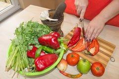 ` S женщины вручает перец вырезывания, за свежими овощами Кашевар женщины на кухне Стоковая Фотография