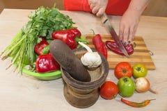 ` S женщины вручает перец вырезывания, за свежими овощами Кашевар женщины на кухне Стоковое Изображение