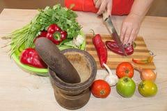 ` S женщины вручает перец вырезывания, за свежими овощами Кашевар женщины на кухне Стоковые Фотографии RF