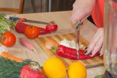 ` S женщины вручает перец вырезывания, за свежими овощами Кашевар женщины на кухне Стоковое Фото