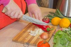 ` S женщины вручает перец вырезывания, за свежими овощами Кашевар женщины на кухне Стоковые Изображения