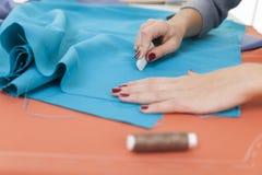 ` S женщины вручает рисовать картину на ярком голубом материале Стоковые Фото
