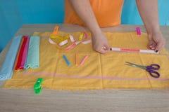 ` S женщины вручает рисовать картину на ярком желтом материале на ее рабочем месте Стоковая Фотография