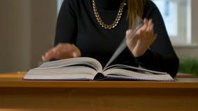 ` S женщин вручает листать через книгу Женщина сидя на таблице листая через книгу акции видеоматериалы
