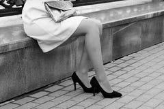 ` S женщин высоко-накренило ботинки, девушку сидя на обочине улицы Стоковые Изображения RF