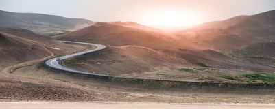 S-изогнутая дорога асфальта водит к горам в вулканической области на времени захода солнца, Исландии Исландская тема поездки Стоковые Изображения