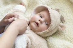 ` S мамы вручает одевать ее маленького сына в костюме оленей стоковая фотография