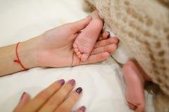 ` S мамы держа в ногах рук крошечных newborn младенца, покрытого knitte Стоковое Фото
