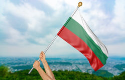 ` S молодого человека вручает гордо развевать национальный флаг Болгарии в небе Стоковое Изображение RF