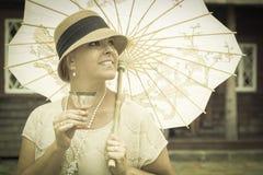 1920s одели девушку с парасолем и портретом бокала вина Стоковые Изображения RF