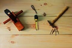 ` S плотника для woodworking Старый самолет молотка и ногтя и древесины и измеряя лента на предпосылке текстуры деревянной Стоковое Изображение RF