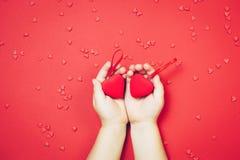 ` S ребенка вручает держать красные сердца на красной предпосылке Взгляд сверху, плоское положение Comcept ` s валентинки St Стоковая Фотография