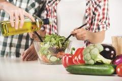 ` S руки молодых пар подготавливает салат в кухне дома Стоковые Изображения RF