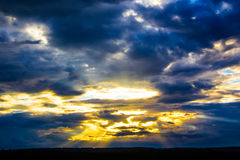 ` S солнца излучает выходящ сквозь отверстие облака Стоковые Фото
