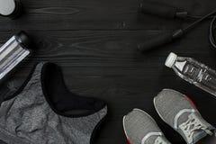 ` S спортсмена установило с женскими одеждой, тапками и бутылкой воды на темной предпосылке Стоковое Изображение