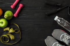 ` S спортсмена установило с женскими одеждой, тапками и бутылкой воды на темной предпосылке Стоковые Фотографии RF