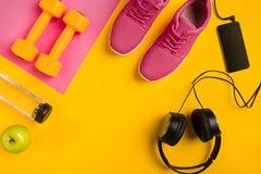 ` S спортсмена установило с женской одеждой, гантелями и бутылкой воды на желтой предпосылке Стоковые Фото