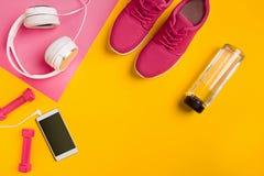 ` S спортсмена установило с женской одеждой, гантелями и бутылкой воды на желтой предпосылке Стоковое фото RF