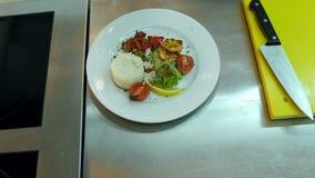 ` S шеф-повара вручает добавлять соус к рису с овощами на плите сток-видео