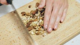 ` S шеф-повара вручает прерывать смешанные гайки на деревянной разделочной доске сток-видео