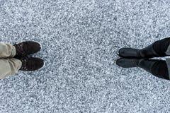 ` S людей и ботинки женщин на грубой предпосылке снега Песчаная снежная покрытая поверхность асфальта Место текста Взгляд сверху Стоковые Фотографии RF