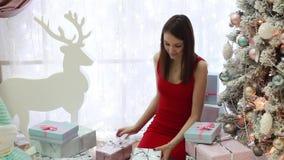 Νέα γυναίκα και πολλά νέα δώρα έτους στο νέο εσωτερικό έτους ` s απόθεμα βίντεο