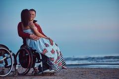 爱恋的夫妇,妇女坐她的丈夫` s膝部,基于海滩反对明亮的黎明的背景 图库摄影