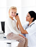 检查她的患者\ 's耳朵的微笑的医生 图库摄影