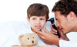 检查患者s的集中的医生耳朵 免版税库存图片